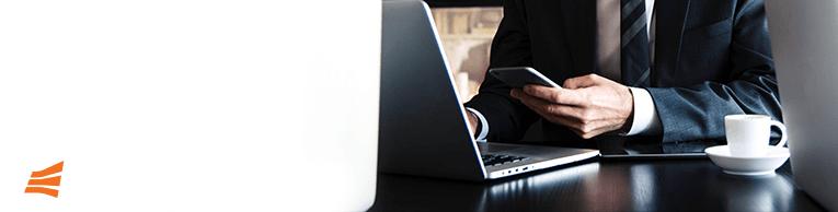 Um homem branco de terno usando o celular e o computador com um café ao lado