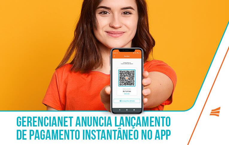 Na imagem: mulher olhando para a câmera com smartphone na mão anunciando novo recurso do app Gerencianet: pagamento instantâneo e transferência entre contas da instituição