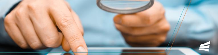 Na imagem: usuário usando lupa sobre um tablet, simbolizando uma análise  mais detalhada para identificar Phishing e outros golpes na internet