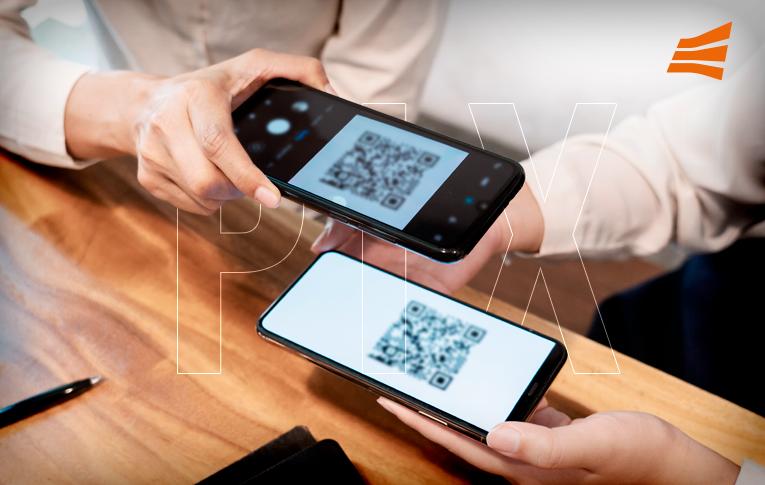 Na imagem: dois celulares sobre a mesa, um deles mostra o QR Code, enquanto o segundo faz a leitura do código para realizar o pagamento instantâneo PIX