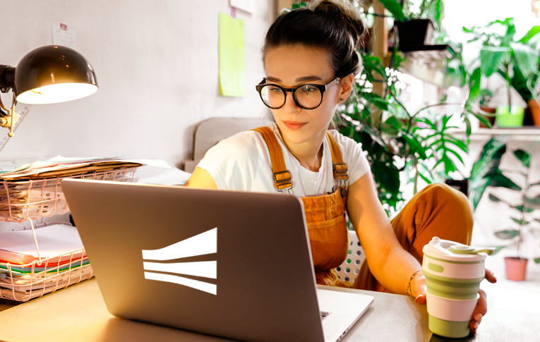 Na imagem: mulher branca, de cabelo castanho, sentada na cadeira, segurando um copo de café e usando o notebook para realizar teletrabalho em seu escritório home office.