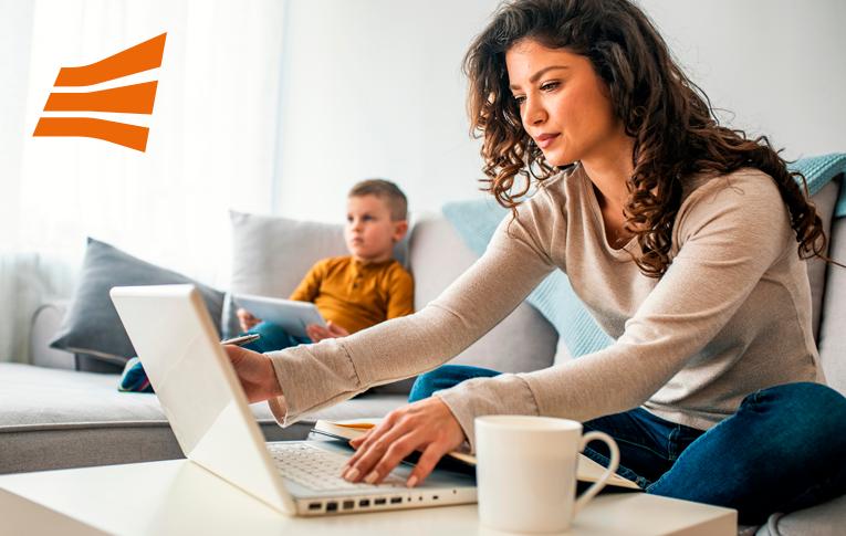 Na imagem: mulher de cabelo cacheado sentada no sofá usando o notebook, mantendo a produtividade no trabalhando em casa durante a quarentena. No fundo desfocado, seu filho sentado no sofá com um tablet na mão enquanto assiste TV.