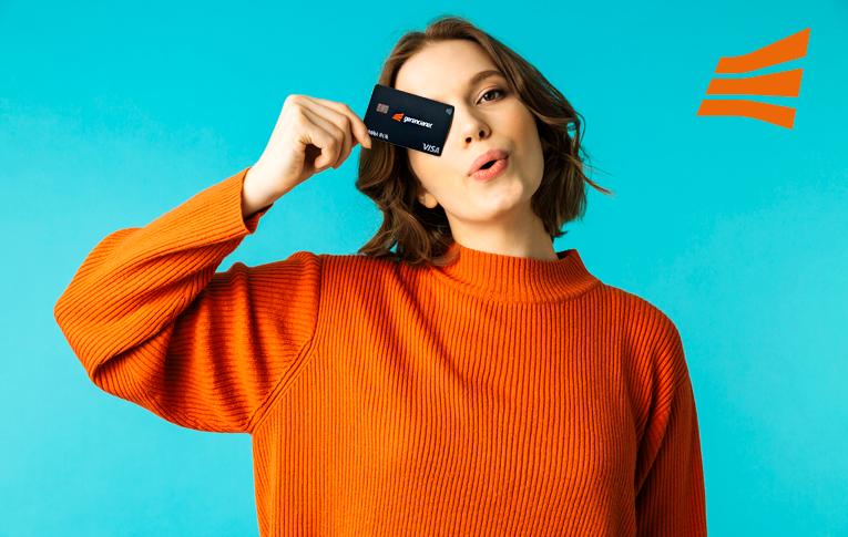 Na imagem: mulher branca usando blusa de tricô laranja, segurando o cartão contactless da Gerencianet em frente o rosto.