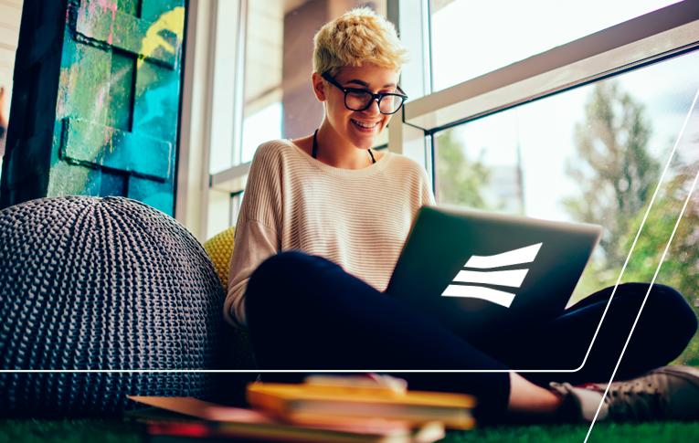 Na imagem: mulher loira usando óculos, sentada no chão com as pernas cruzadas ao lado de uma janela, enquanto segura um notebook no colo. Espaço descontraído com pufs e livros próximos a ela.