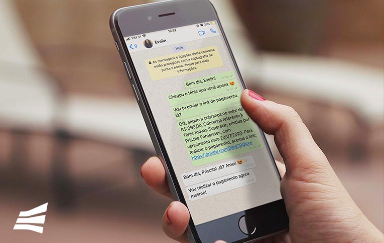 Na imagem: mão feminina segurando um celular com a tela aberta em uma conversa no WhatsAPP, utilizando a ferramenta link de pagamento para emitir uma cobrança