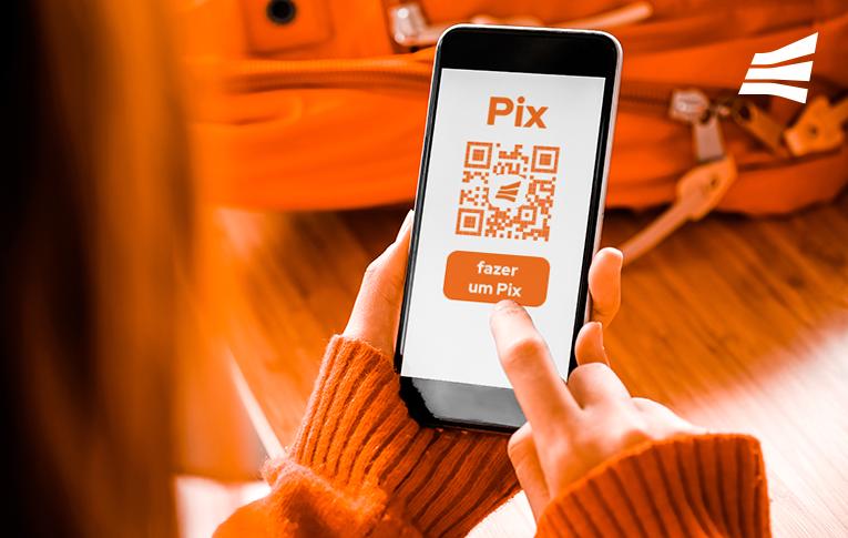 """Na imagem: mãos de uma mulher branca, vestindo uma blusa de tricot laranja, segurando um smartphone. Na tela do celular, aparece o nome Pix, um QR Code com o logo da Gerencianet e um botão escrito """"fazer um Pix"""", indicando uma transação Pix na Gerencianet. Ao fundo da imagem, uma mochila laranja sobre a mesa."""