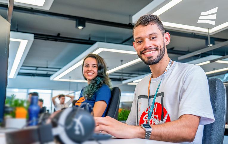 Na imagem: 2 colaboradores da Gerencianet, um homem usando uma camisa branca e uma mulher usando camisa azul, com o logo da Gerencianet. Ambos sentados, na mesa de trabalho, olhando em direção à câmera e sorrindo.