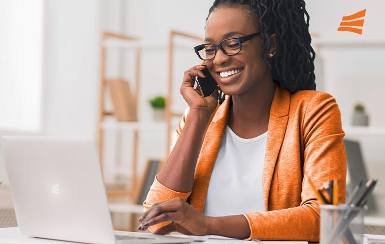 Na imagem: mulher negra, vestindo um blazer laranja, sorrindo enquanto usa um notebook e conversa com o cliente pelo celular, na estratégia de custommer success.
