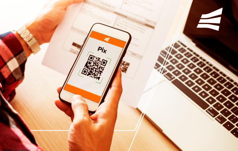 Na imagem: uma mão segurando o smartphone enquanto lê o QR Code de um papel impresso, para pagar com Pix.