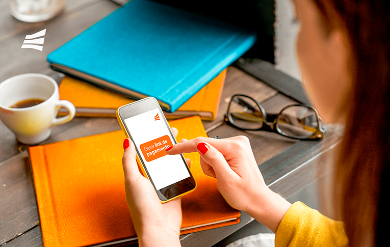 Mulher acessando o celular para aprender como gerar link de pagamento. Na imagem, há uma mesa com livros, óculos e xícara de café.