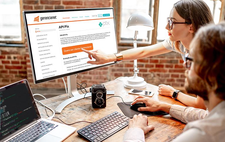 Na imagem: pessoa sentada usando o computador, enquanto uma outra pessoa aponta para a tela. Na tela, aparece a documentação da API Pix Gerencianet.