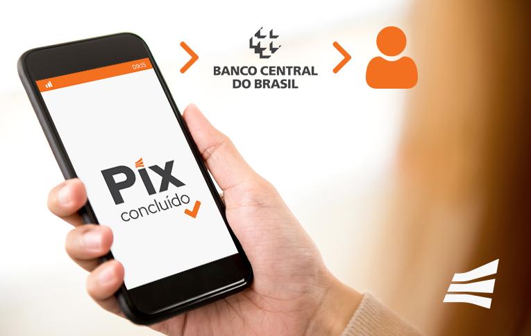 Uma mão segurando um smartphone. Na tela está escrito: Pix concluído.
