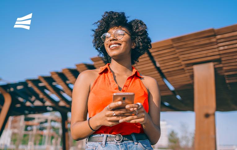 Mulher negra sorrindo com um smartphone nas mãos pesquisando como pagar com Pix.