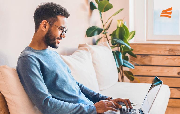 Homem sorrindo, sentado no sofá com o notebook no colo durante seu processo de autodesenvolvimento.
