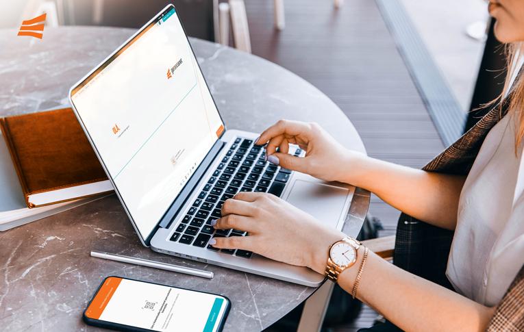 Mulher acessando notebook e celular para conhecer a segurança digital da conta Gerencianet