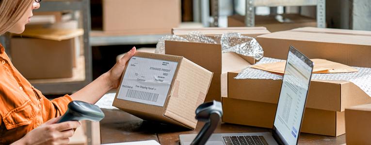 Mulher rodeada de caixas, usando um leitor de código para organizar as vendas do seu e-commerce.