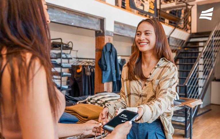 Mulher fazendo pagamento pelas compras no comércio varejista de roupas com Pix, por meio do seu smartphone