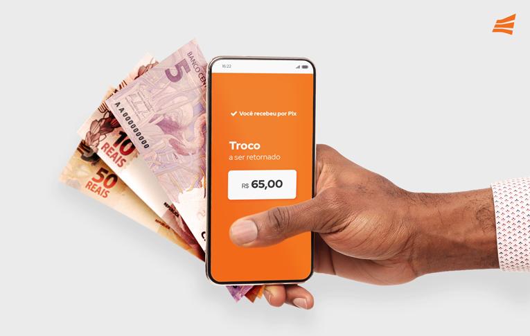 Pix Saque e Pix Troco: mão segurando smartphone e cédulas de dinheiro
