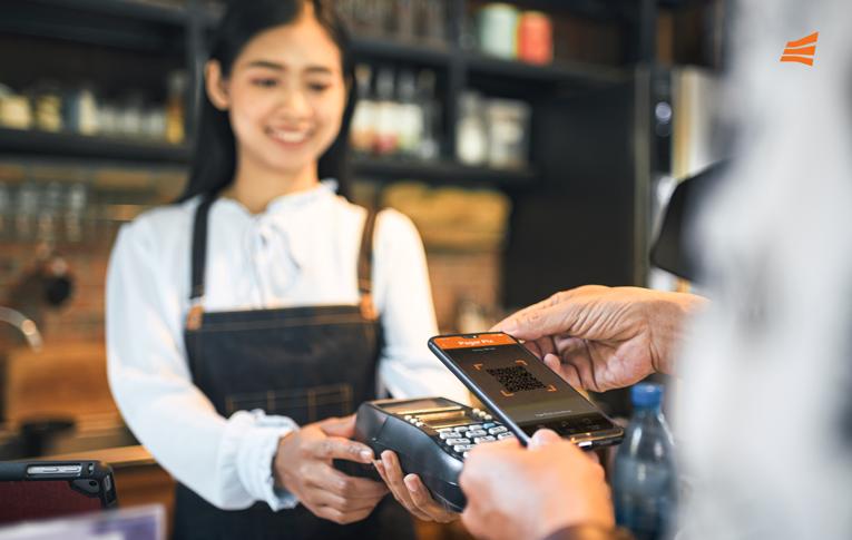 Atendente recebendo pagamento pelo Pix integrado à maquininha de cartão, enquanto o cliente usa o seu smartphone para ler o QR Code