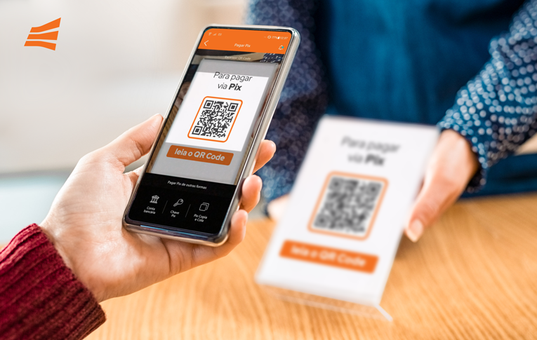 Comerciante segura a plaquinha com QR Code Pix para PJ impresso, enquanto o pagador utiliza o smartphone para realizar o pagamento via Pix