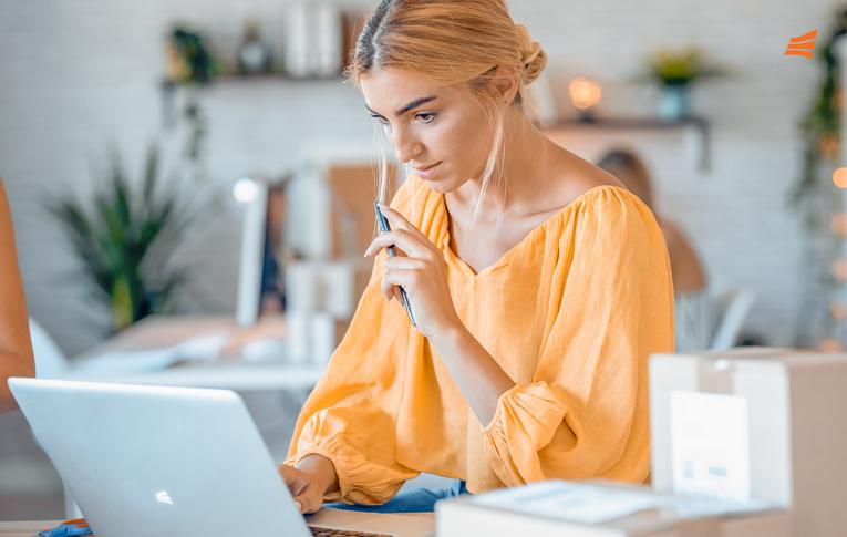 Mulher loira sentada de frente para um notebook com uma caneta nas mãos. Na mesa há algumas caixas para a black friday 2021.