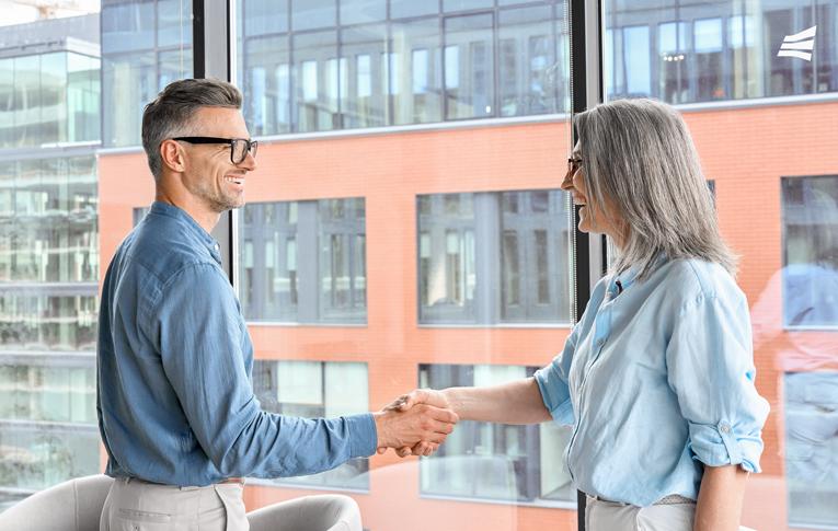 Duas pessoas sorrindo e apertando as mãos sinalizando bom negócio no pós-venda, em uma sala com janela de vidro e prédios ao fundo