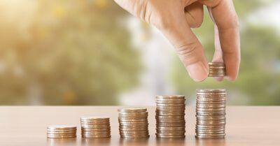 Mão de uma pessoa montando diversas pilhas de moedas