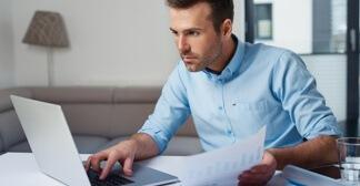 Homem de camisa trabalhando em um notebook