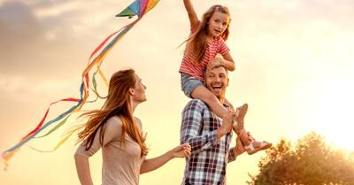 Família (pai, mãe e criança no ombro dos pais) correm; criança segurando uma pipa