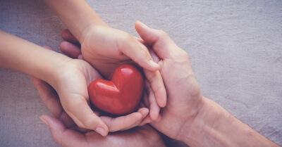 Mãos de uma pessoa adulta e uma criança sobrepostas com uma peça em formato de coração no centro