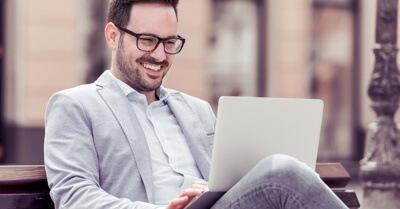 Homem de terno sentado em um banco mexendo em um notebook