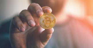 Mão de uma pessoa segurando uma moeda com o logo do Bitcoin