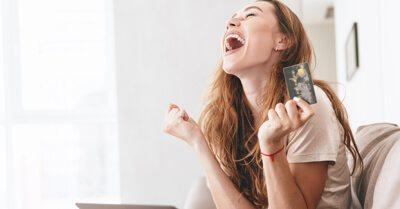 Mulher comemorando segurando um cartão de crédito na mão