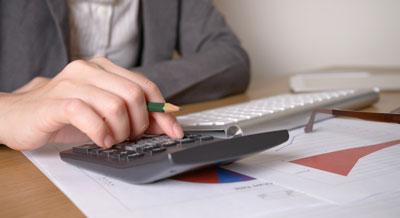 Mão de uma pessoa segurando um lápis e fazendo conta em uma calculadora.