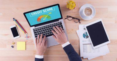 Homem teclando num computador e na tela aparece um gráfico com resultados de um credit score