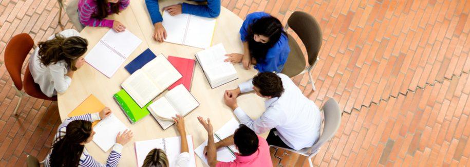 Mesa redonda com 8 homens e mulheres, debruçados em cima de um caderno