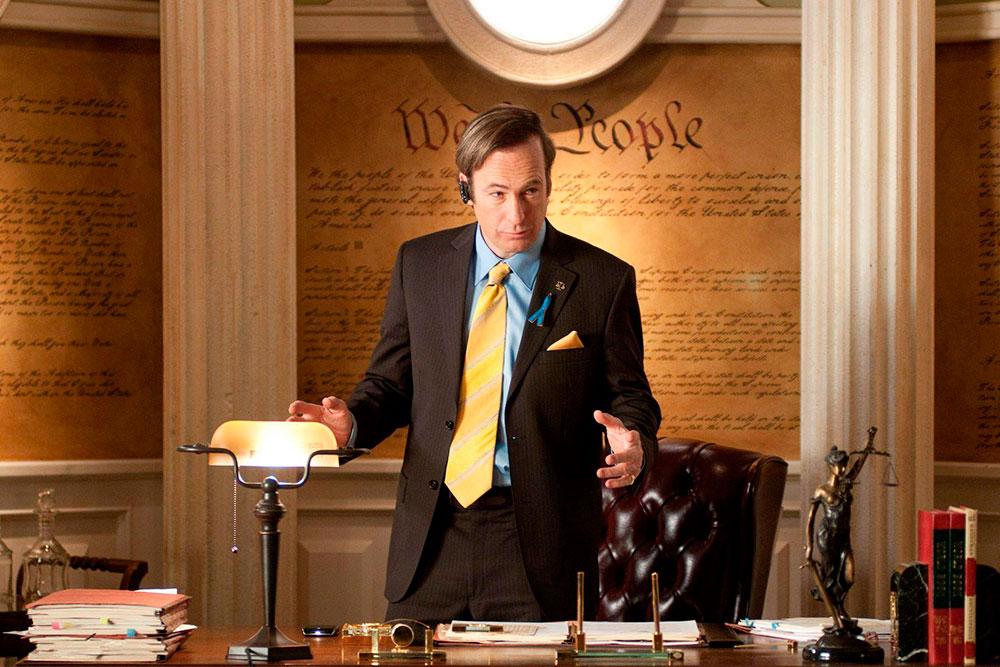 Um advogado atrás de uma mesa conversando com seu cliente