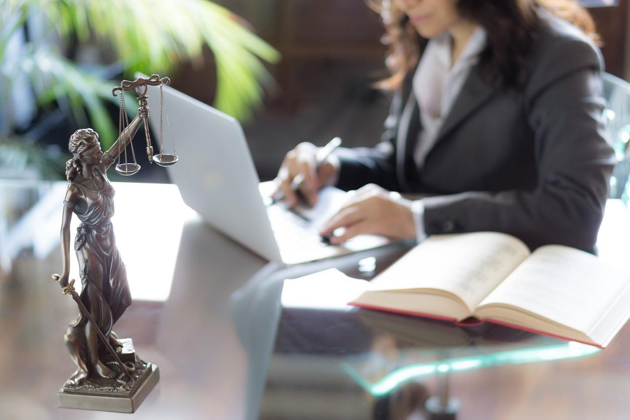 O que faz um promotor de justiça? | Promotora trabalhando em sua mesa