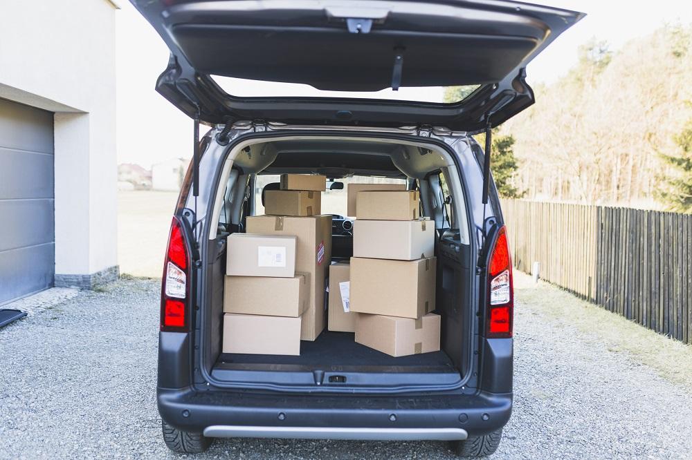 Carro adequado para frete com porta-malas aberto e caixas dentro