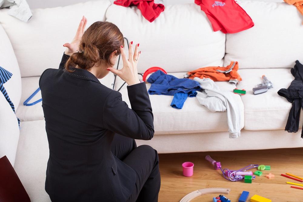 Mulher apavorada olhando para o sofá cheio de roupas bagunçadas