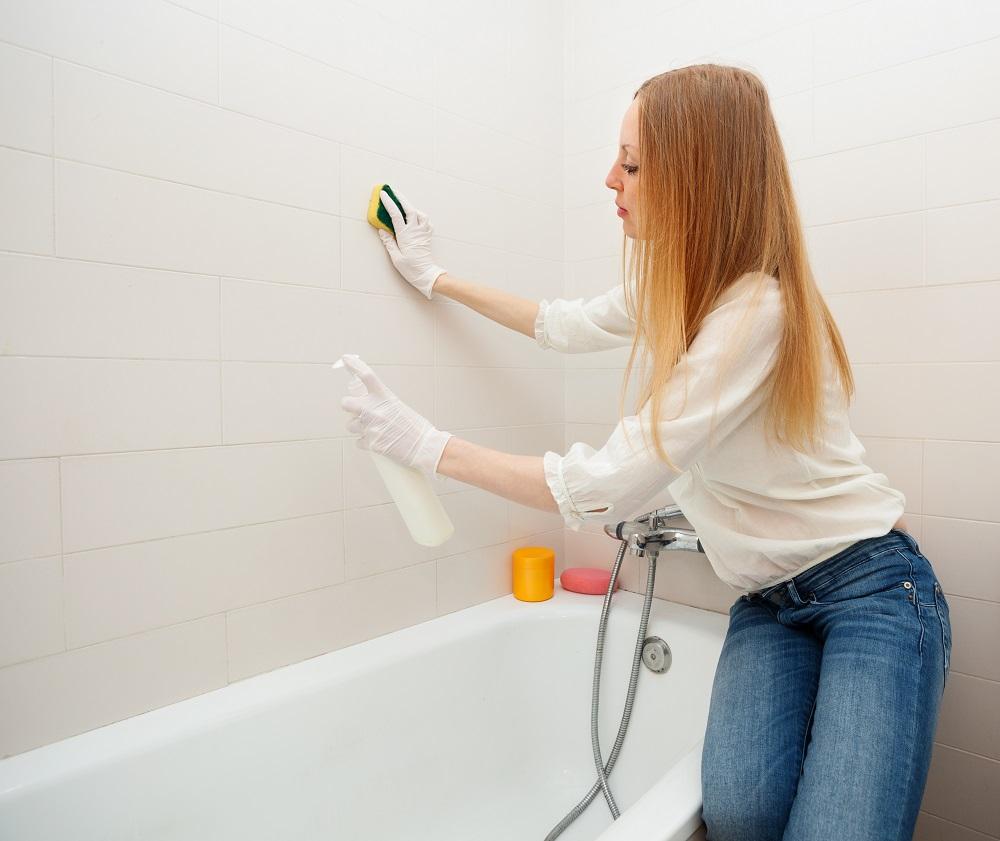 Mulher loira limpando banheira e azulejos do banheiro