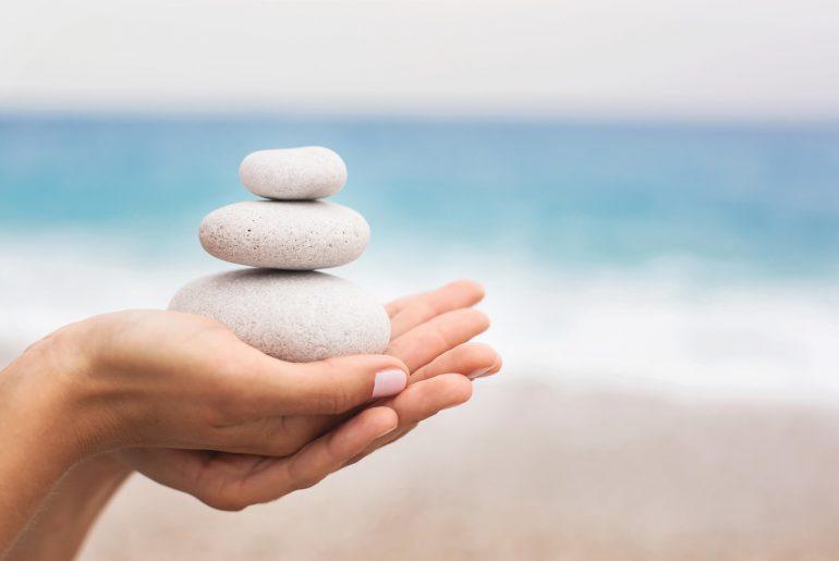 mãos com pedras enérgicas para feng shui