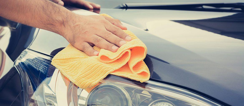 Mão masculina com pano de microfibra fazendo lavagem ecológica no carro preto