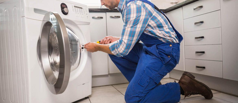 Homem realizando conserto de máquina de lavar
