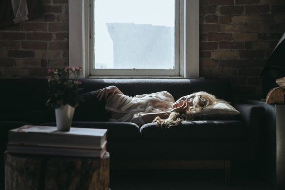 Absenteísmo: mulher deitada no sofá com rosto transparecendo tristeza