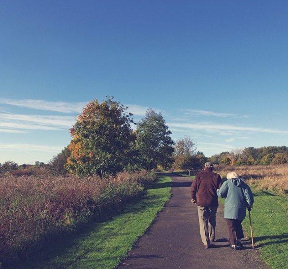 Aposentadoria por idade: dois idosos caminhando em uma estradinha no campo