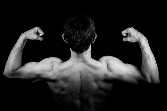 Alimentação para ganhar massa muscular: Homem contraindo os músculos do braço