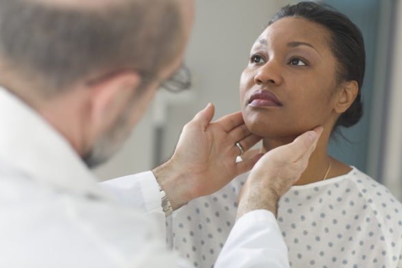 Hipotireoidismo: médico verificando o tamanho da glândula tireoide de uma paciente com as suas duas mãos