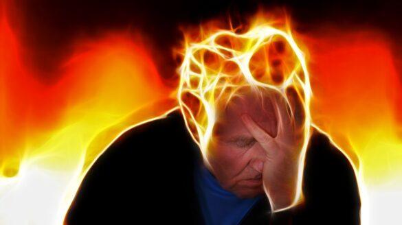 Homem com uma de suas mãos no rosto junto de uma ilustração de labaredas de fogo saindo de sua cabeça, e exemplificando figurativamente como é a síndrome de burnout
