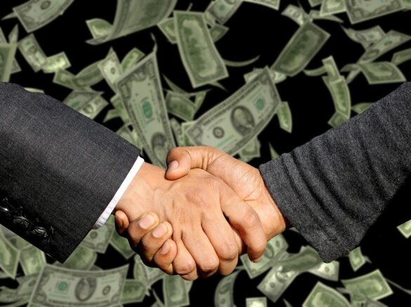Investidor anjo: aperto de mão entre homens de terno com plano de fundo de notas de dinheiro